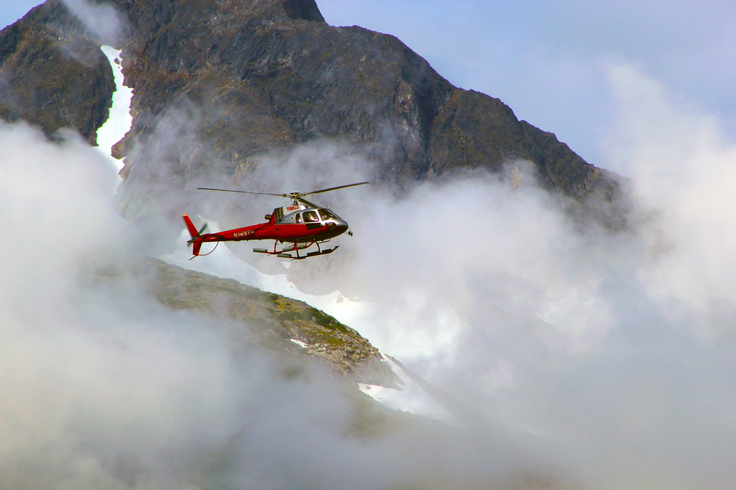 red-helicopter-on-top-of-foggy-mountain-826311